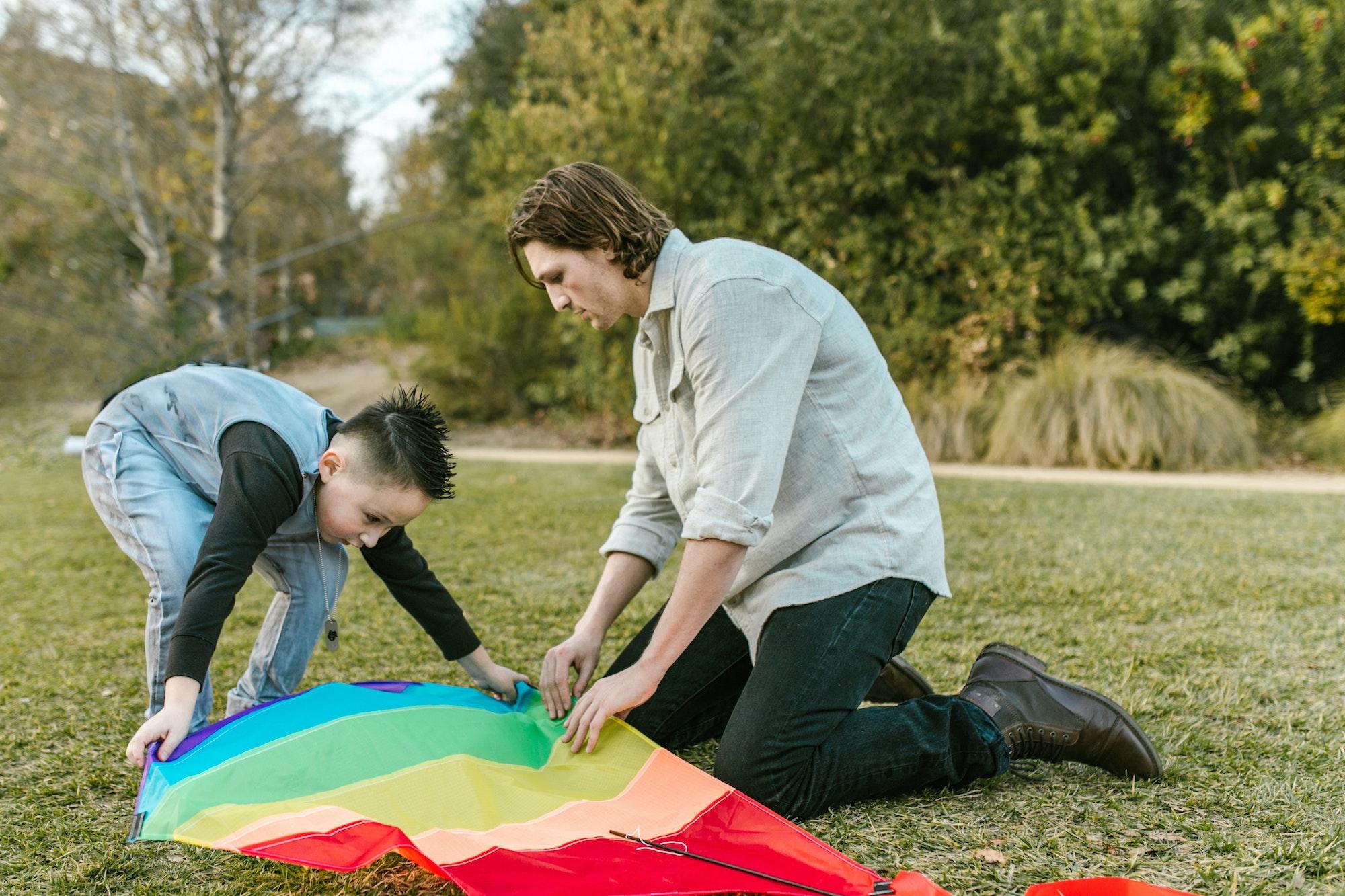 Mann in Jeanshemd und dunkler Hose legt mit Jungen in Jeansweste und Jeanshose einen Drachen auf einer Wiese aus