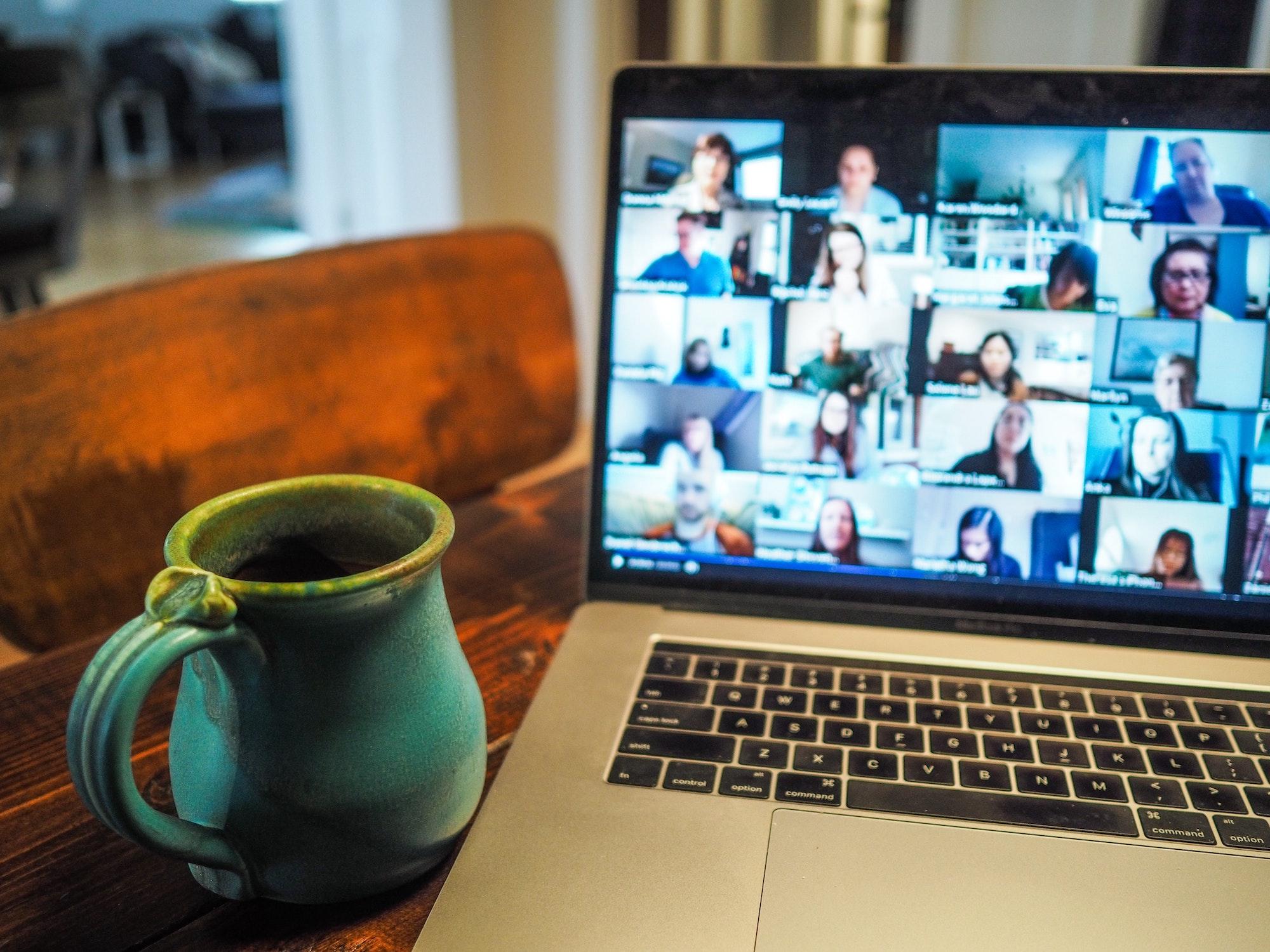 Laptop zeigt verschiedene Menschen in einer Videokonferenz, daneben steht eine Tasse