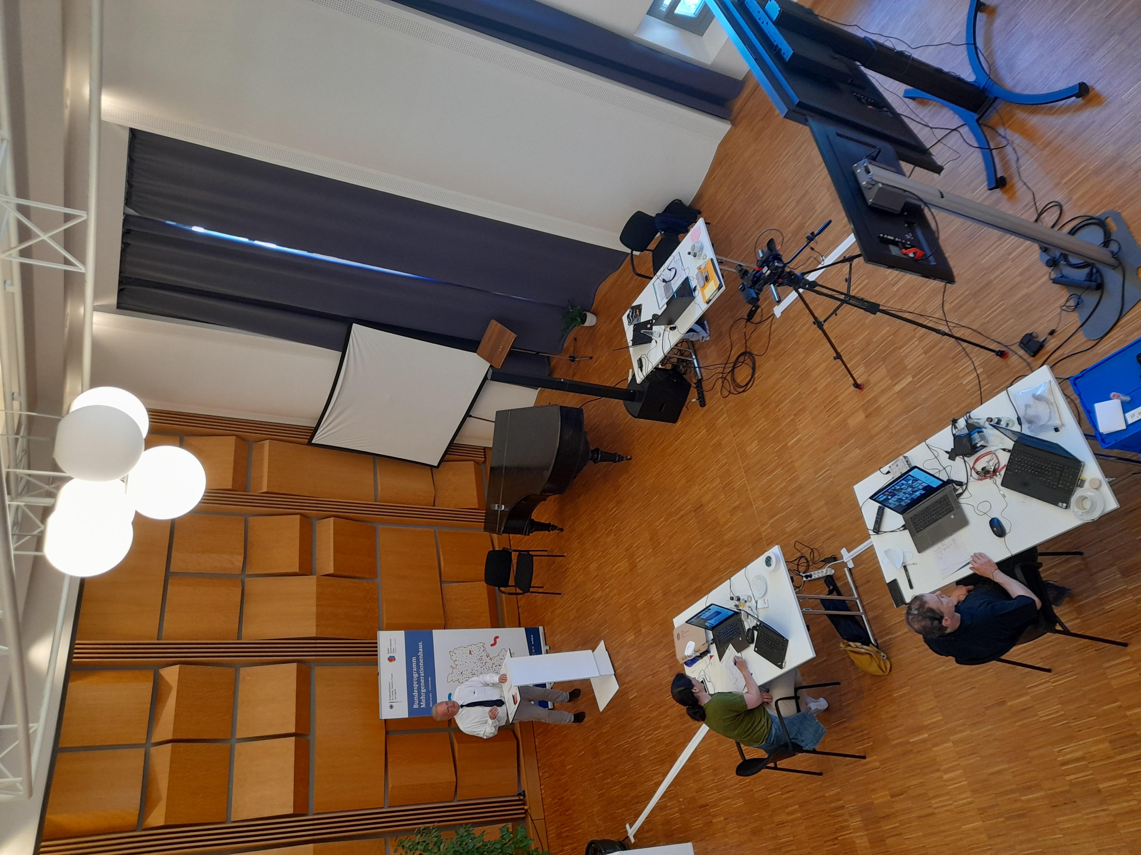 Blick von oben auf Aufbau des Fachtags mit Moderator am Pult und zwei Personen an Schreibtischen mit Laptops