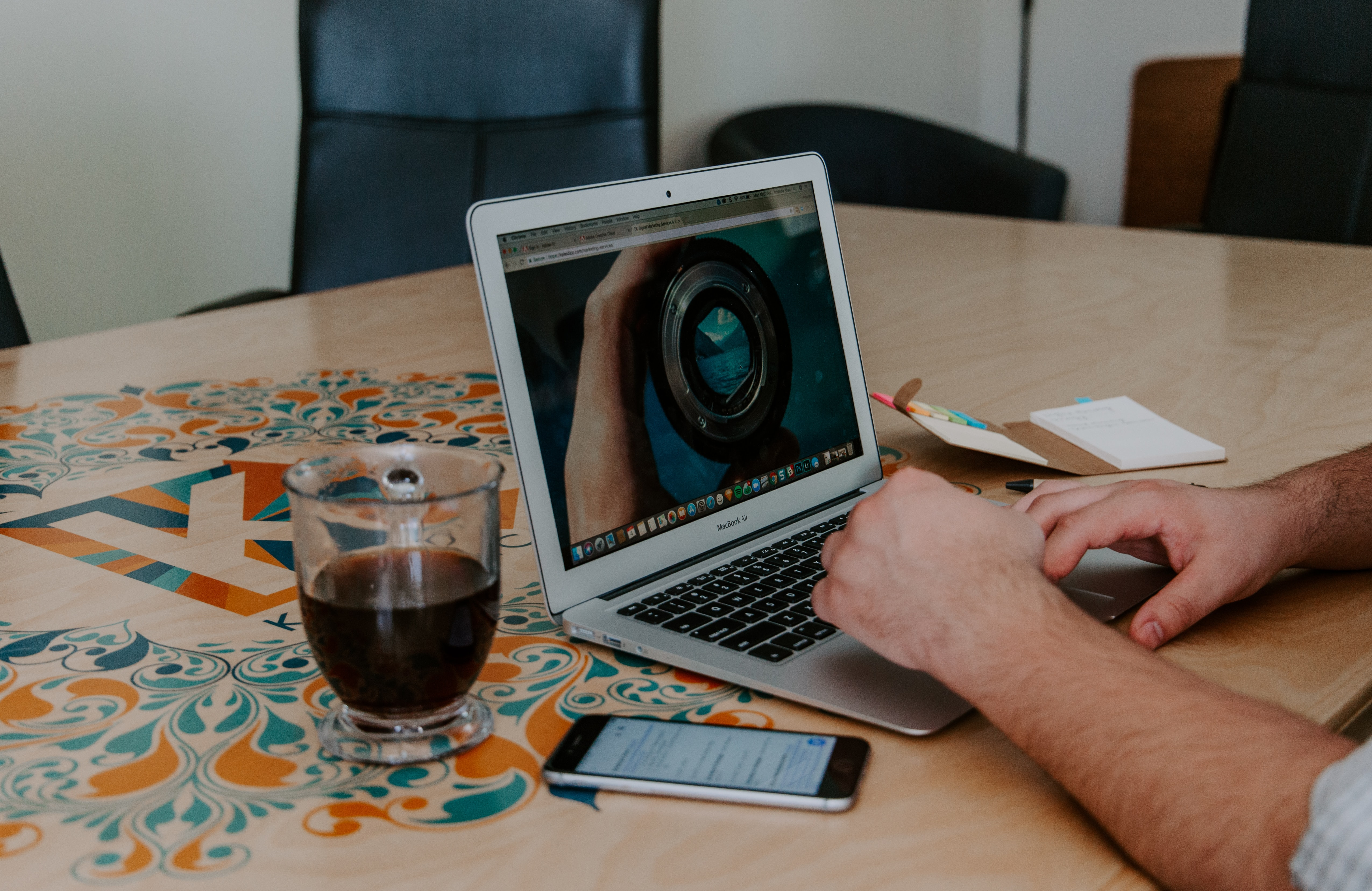 Ein aufgeklappter Computer, ein paar Hände, die zum Computer greifen. Daneben steht ein Getränk.