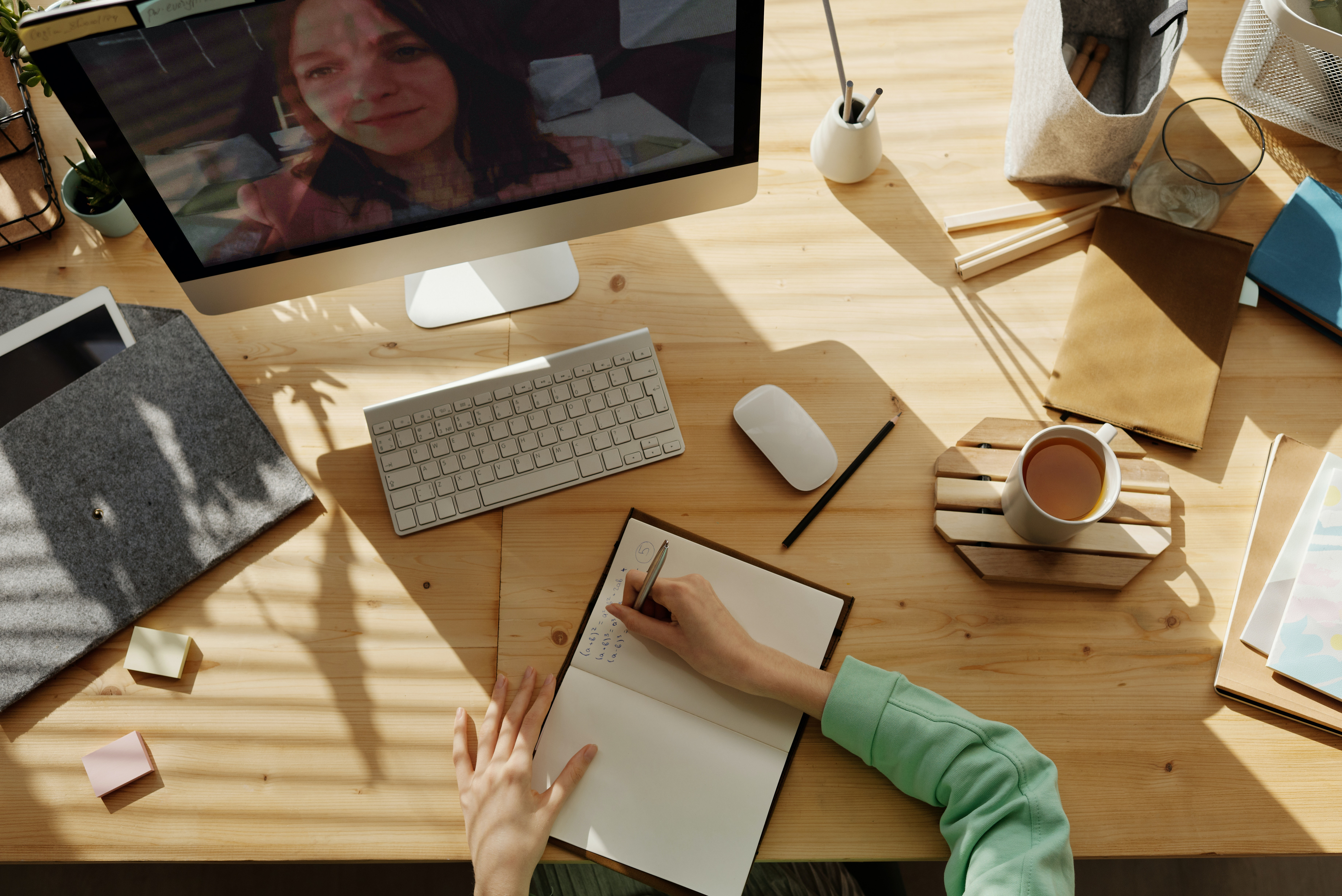 Schreibtisch von oben, Hände liegen auf einem Notizbuch, auf einem Computerbildschirm ist Kopf einer Frau abgebildet