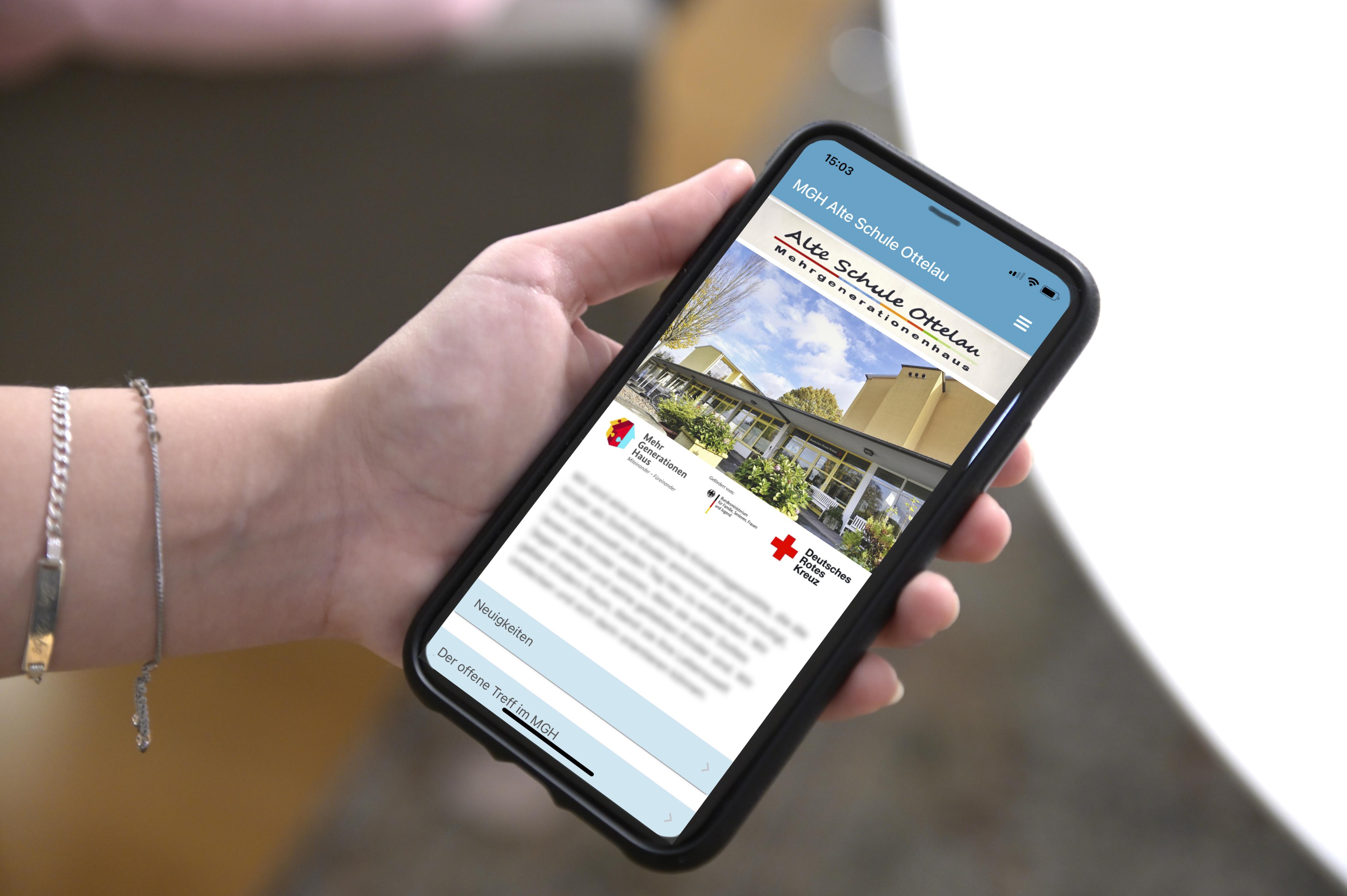 Hand hält ein Handy, auf dem die App des Mehrgenerationenhauses Alte Schule Ottelau zu sehen ist