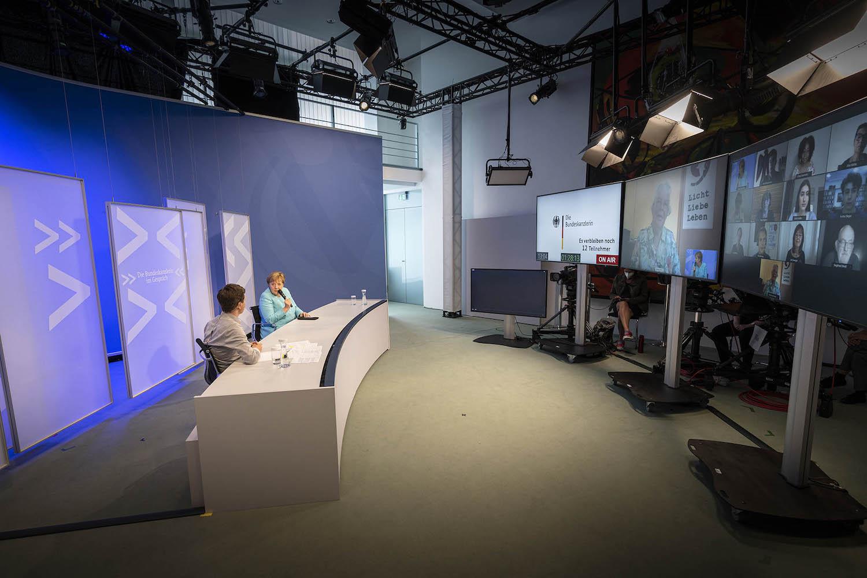Bundeskanzlerin Angela Merkel sitzt an einem Tisch mit Blick auf Bildschirme, die eine Videokonferenz zeigen