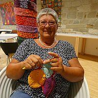 Ingrid Thieler sitzt auf einem Stuhl und strickt.