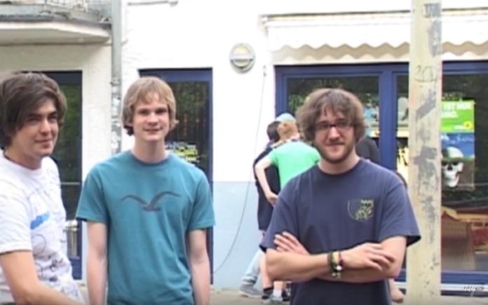 Drei junge Männer stehen in einem Kreis und gucken in die Kamera.