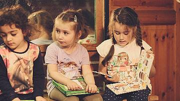 Drei Kinder lesen in Büchern.