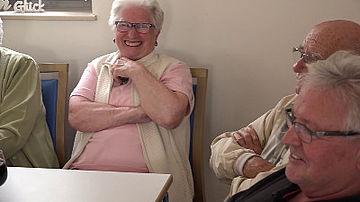 Vier ältere Menschen sitzen an einem Tisch.