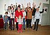 Auf dem Foto sind 12 PErsonen unterschiedlichen alters abgebildet, die die Arme in die Luft strecken.