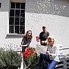 Drei Personen sind vor einem Haus zu sehen. Eine junge Frau links hat eine Konfetti-Kanone abgefeuert, überall schwirrt Konfetti herum. Ein Mann mit Kappe hält die Gewinner-Trophäe in den Händen, im Vordergrund zeigt eine blonde Frau die Gewinner-Urkunde und lacht.