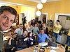 Auf dem Foto sind 13 Personen abgebildet, die vor einem Bildschirm sitzen und sich freuen.