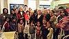 Gruppenfoto mit rund zwanzig Personen. Einige sind geflüchtete Frauen mit kleinen Kindern.