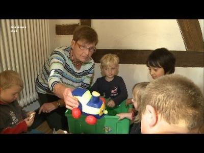 Eine Frau und fünf Kinder sitzen auf dem Boden und spielen.