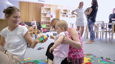 Zwei Frauen sitzen auf dem Boden und spielen mit einem Kleinkind.