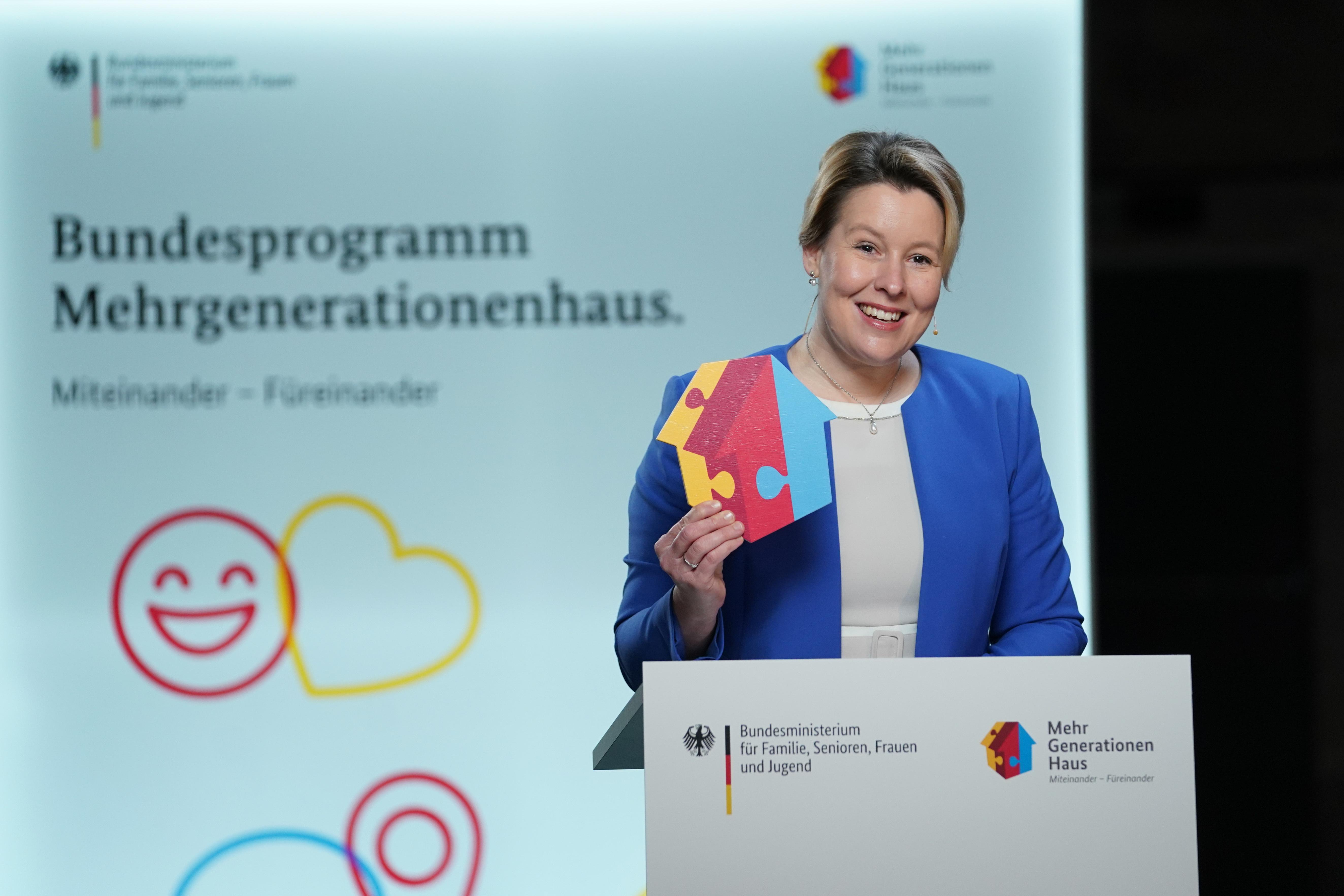 Bundesfamilienministerin Franziska Giffey steht am Rednerpult mit dem MGH-Häuser-Logo in der Hand