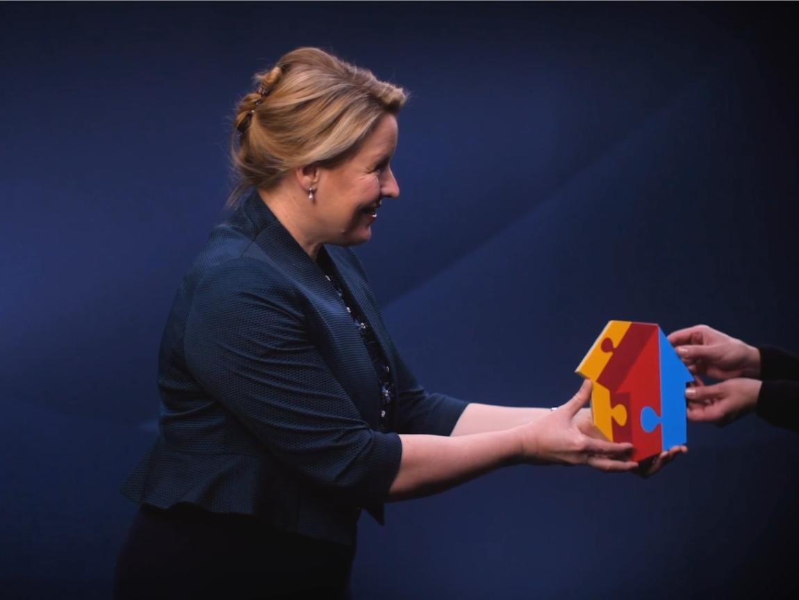 Bundesfamilienministerin Franziska Giffey vor einer dunkelblauen Wand, sie gibt das MGH-Logo als 3D-Version aus dem rechten Bildrand heraus.