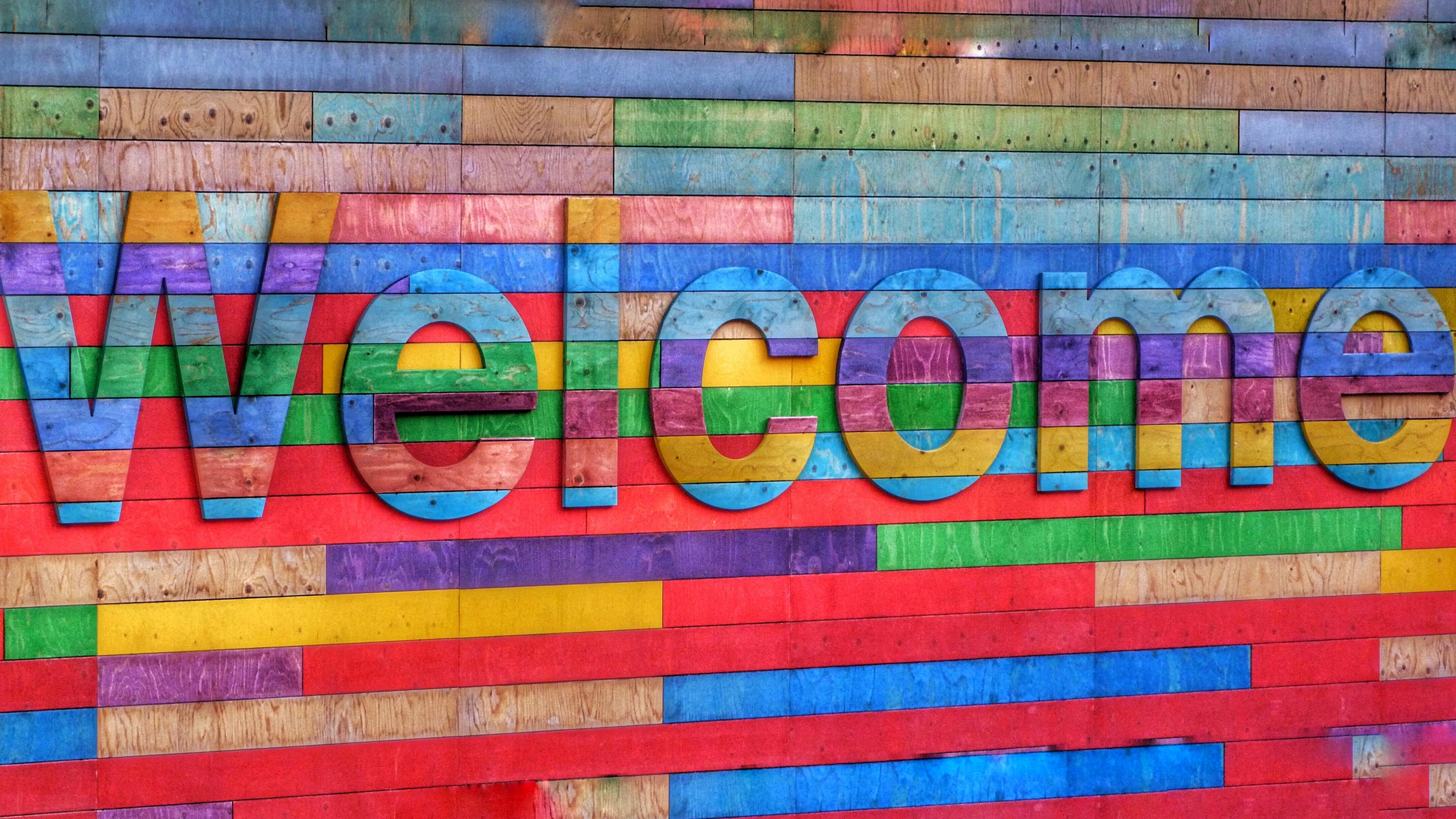 Auf einer bunten Wand steht Welcome