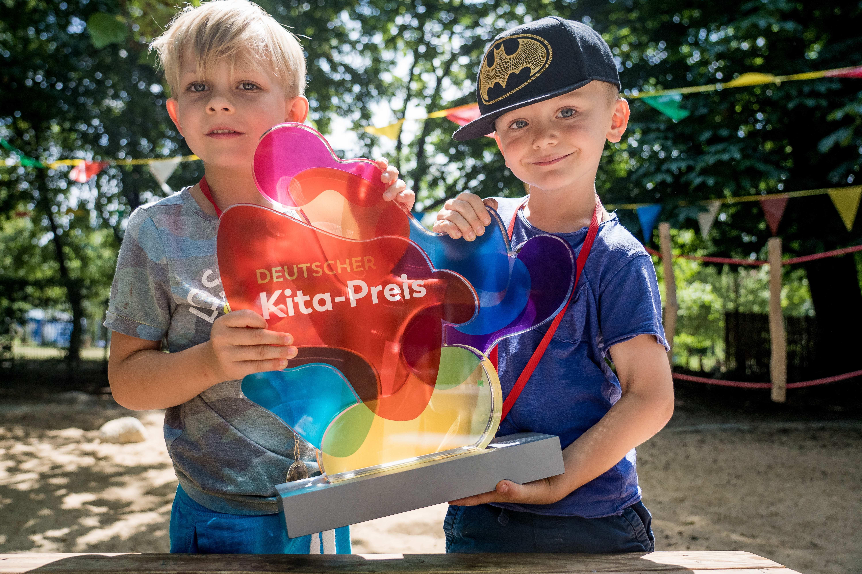 Zwei Kinder halten die Trophäe des Deutschen Kita-Preises stolz in die Kamera